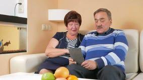 Uomo senior felice e donna che parlano sul PC della compressa a casa con i bambini Il video che chiama via Internet contribuisce  stock footage