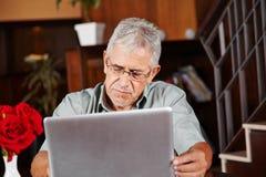 Uomo senior in hotel con il computer della compressa Fotografia Stock