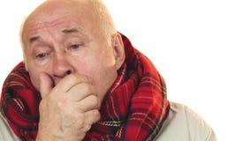 Uomo senior malato e malato che porta una sciarpa che tossisce sguardo stanco fotografia stock