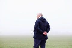 Uomo senior nel campo nebbioso da dietro Fotografie Stock Libere da Diritti