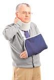 Uomo senior nel dolore con un braccio rotto che tiene il suo collo Fotografia Stock