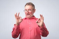 Uomo senior nel segno GIUSTO di rappresentazione rossa della camicia immagini stock