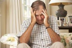 Uomo senior pensionato infelice che si siede su Sofa At Home Fotografia Stock