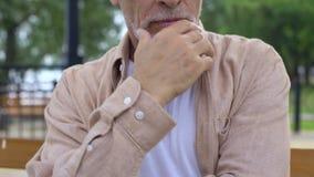 Uomo senior premuroso che si siede sul banco di parco, età di pensionamento, decisione seria video d archivio