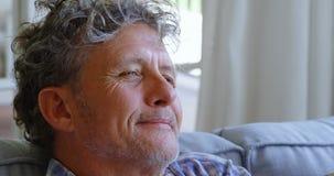 Uomo senior premuroso che si siede sul sofà a casa 4k archivi video