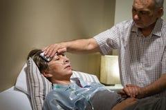 Uomo senior preoccupantesi che aiuta la sua moglie malata Immagini Stock