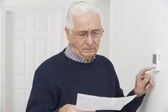 Uomo senior preoccupato con Bill Turning Down Central Heating termo fotografia stock libera da diritti