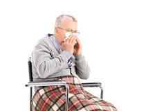 Uomo senior in sedia a rotelle che soffia il suo naso in un tessuto Immagini Stock
