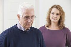 Uomo senior serio con la figlia adulta a casa Immagine Stock Libera da Diritti