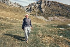 Uomo senior serio sulla strada delle montagne Fotografie Stock Libere da Diritti