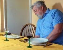 Uomo senior solo alla tavola di cena immagini stock libere da diritti