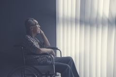 Uomo senior solo triste che si siede sulla sedia a rotelle immagine stock libera da diritti
