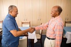 Uomo senior sorridente che fa stretta di mano con l'amico Fotografia Stock