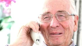 Uomo senior sorridente che parla sul telefono a casa stock footage