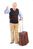 Uomo senior sorridente che tiene i suoi bagagli e che dà pollice su Fotografia Stock Libera da Diritti