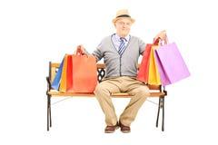 Uomo senior sorridente messo su un sacchetto della spesa della tenuta del banco di legno Immagini Stock