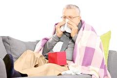 Uomo senior su un sofà che soffia il suo naso in un fazzoletto Fotografia Stock Libera da Diritti