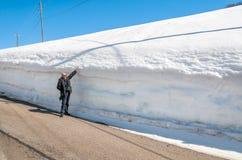 Uomo senior sul bordo della strada con un'alta accumulazione di neve Immagine Stock