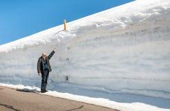 Uomo senior sul bordo della strada con un'alta accumulazione di neve Immagini Stock