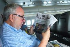 Uomo senior sul volo di Quantas dall'Australia negli Stati Uniti che legge giornale australiano Brisbane Queensland Australia cir fotografia stock