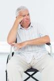 Uomo senior triste che si siede in sedia a rotelle Immagine Stock