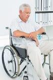 Uomo senior triste che si siede in sedia a rotelle Immagine Stock Libera da Diritti