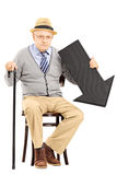 Uomo senior triste che si siede sul banco con la freccia nera che indica giù Fotografie Stock Libere da Diritti