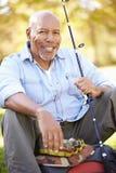 Uomo senior vacanza in campeggio con la canna da pesca Fotografie Stock