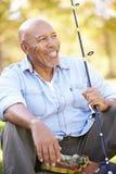 Uomo senior vacanza in campeggio con la canna da pesca Fotografie Stock Libere da Diritti