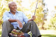 Uomo senior vacanza in campeggio con la canna da pesca Immagine Stock