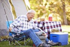 Uomo senior vacanza in campeggio con la canna da pesca Immagini Stock Libere da Diritti