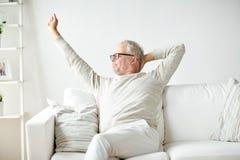 Uomo senior in vetri che si rilassano sul sofà Immagini Stock Libere da Diritti