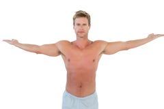 Uomo senza camicia che apre il suo armi Immagine Stock