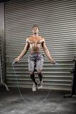Uomo senza camicia che salta la corda immagine stock