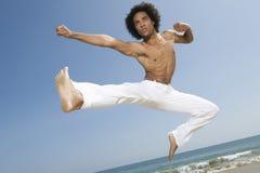 Uomo senza camicia che salta sulla spiaggia Fotografie Stock