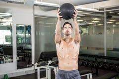 Uomo senza camicia che si esercita con la palla medica Fotografie Stock Libere da Diritti