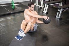 Uomo senza camicia che si esercita con la palla medica Fotografia Stock