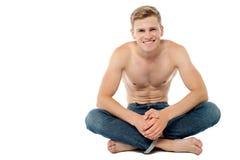 Uomo senza camicia che si siede sul pavimento Immagine Stock