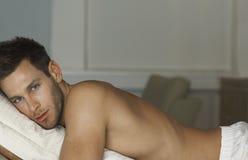 Uomo senza camicia che si trova a letto Fotografia Stock