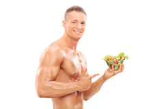 Uomo senza camicia che tiene un'insalata Immagine Stock