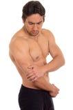 Uomo senza camicia muscolare con dolore del gomito Fotografia Stock
