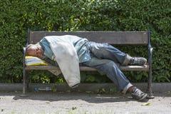 Uomo senza casa che dorme su un banco fotografie stock