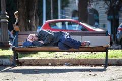 Uomo senza casa che dorme sul banco povertà Fotografie Stock