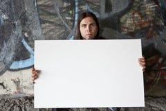 Uomo senza casa che tiene un segno in bianco Fotografia Stock Libera da Diritti