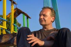 Uomo senza casa Gente povera nel campo da giuoco del ` s dei bambini a sunse Immagine Stock Libera da Diritti