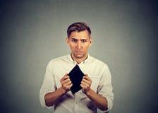Uomo senza soldi che tengono portafoglio vuoto immagine stock libera da diritti