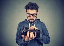 Uomo senza soldi che tengono un portafoglio vuoto fotografia stock libera da diritti