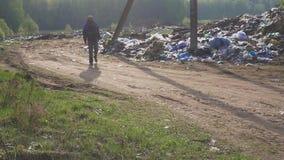 Uomo senza tetto che cammina lungo il mucchio di immondizia nello scarico Fame e povertà archivi video