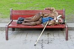 Uomo senza tetto che dorme su un banco fotografia stock