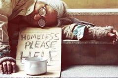 Uomo senza tetto che dorme sulla via del passaggio pedonale nella capitale fotografia stock libera da diritti